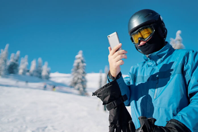 young skier looking at his cell phone after a run down the snow slope