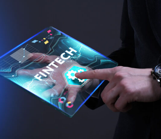 man holding digital virtual tablet and selecting FinTech