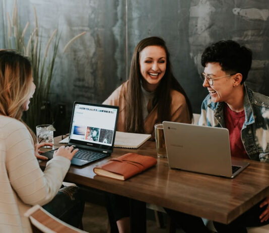 3 girls around a table with laptops laughing and excited about their careers