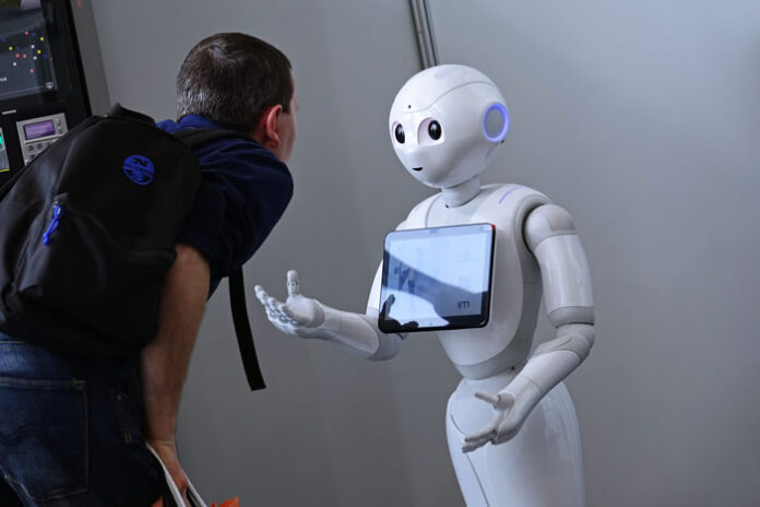 robot coming to greet a man that is leaning over