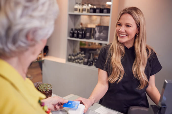 older woman using tech to pay for service at salon with younger attendee girl smiling
