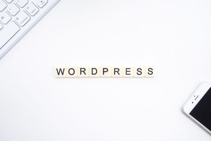 WordPress in Scrabble game letters on a desk with a keyboard and cell phone
