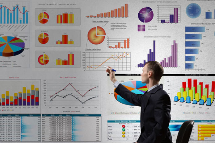 business man pointing to large electronic dashboard with colorful graphs and charts