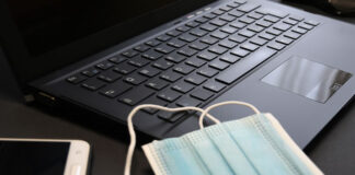 covid masks laying on a tech laptop keyboard