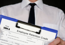 young man holding a federal form 5884-A employee retention credit