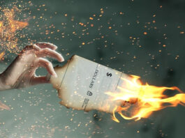 woman holding a paper that is on fire signifying the cost of paper