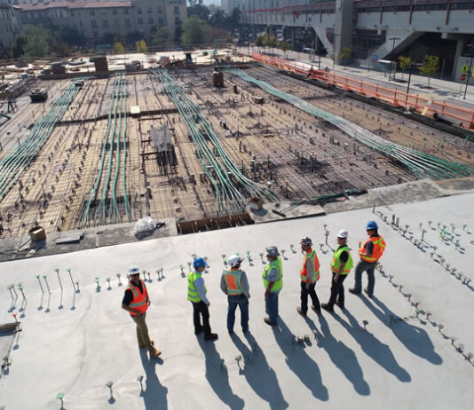 construction site with several men surveying the area using digital construction management