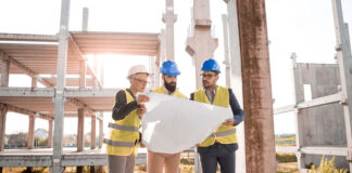 three construction engineers looking at plans and analytic reports