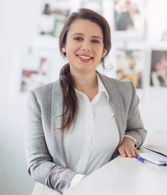Melanie Aronson smiling in grey suit jacket
