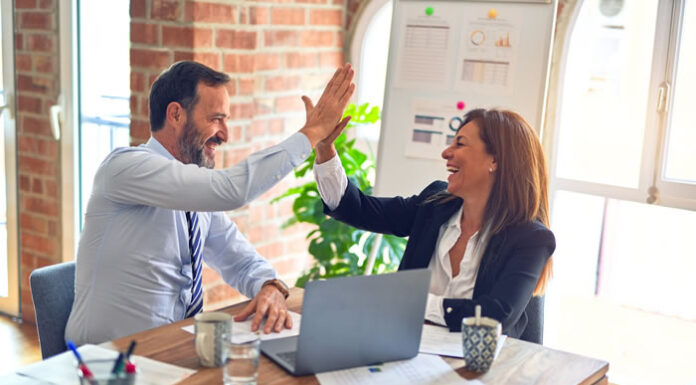 two employees high-fiving because they met their goals