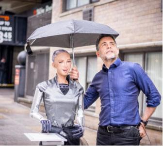 Sophia the Robot and Dr. David Hanson posing under an umbrella