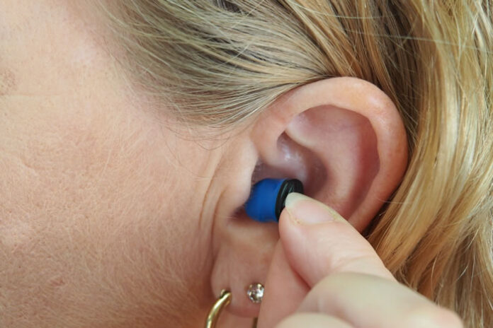 woman putting hearing loss device in her ear