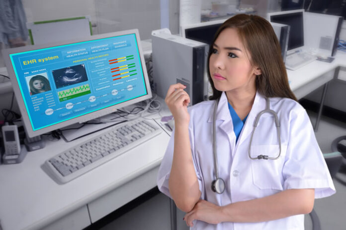 female medical provider looking at electronic health system