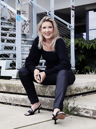 smiling Yvonne Dam sitting on steps looking into camera