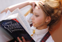 girl intently reading a book in her quest for continual learning