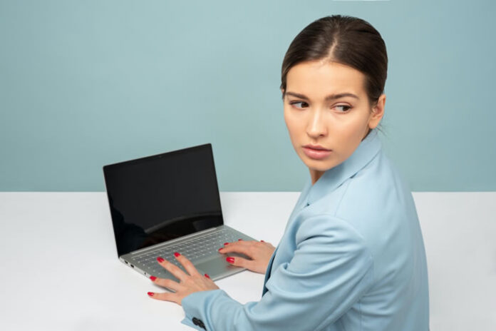 girl typing on her business laptop while suspiciously looking over her shoulder