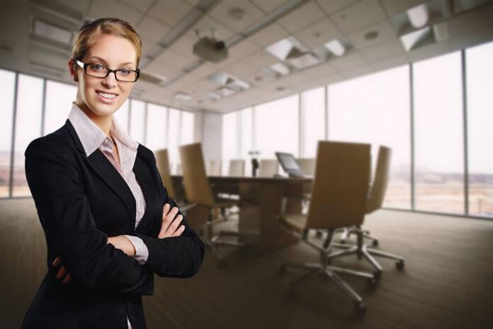 woman healthcare entrepreneur in board room smiling at camera