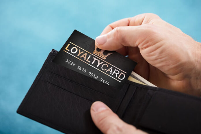 man pulling loyalty program card from his wallet