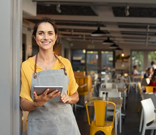 smiling restaurant owner with tablet using smart tech innovation