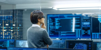 young man reviewing programming code in a data center