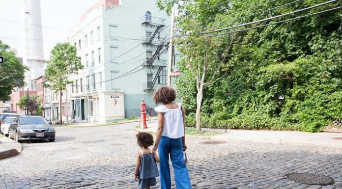 woman and toddler walking in their neighborhood